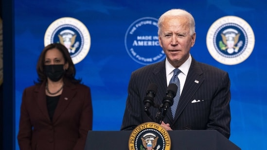 """U.S. President Joe Biden delivers remarks on strengthening American manufacturing with U.S. Vice President Kamala Harris, left, at the Eisenhower Executive Office Building in Washington, D.C., U.S., on Monday, Jan. 25, 2021. President Biden will sign an executive order today to boost federal agencies' purchases of U.S. products, fulfilling a campaign pledge to lay out a """"Buy American"""" plan. Photographer: Kevin Dietsch/UPI/Bloomberg(Bloomberg)"""