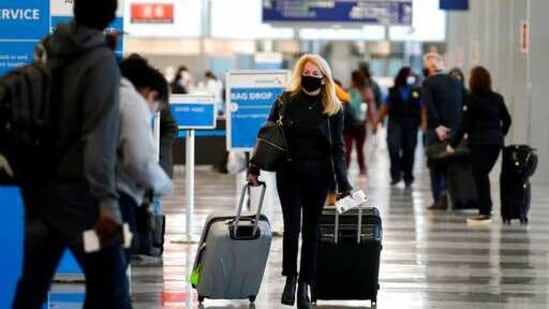 A traveler wears a mask as she walks through Terminal 3 at O'Hare International Airport in Chicago.(AP File Photo )