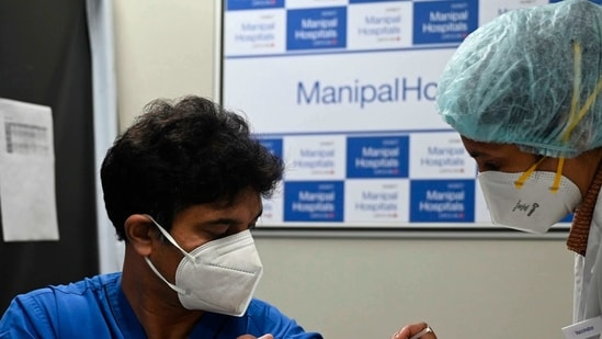 A medical worker (R) inoculates a medical staff with a Covid-19 coronavirus vaccine at the Manipal Hospital, in New Delhi. (Photo by Money SHARMA / AFP)