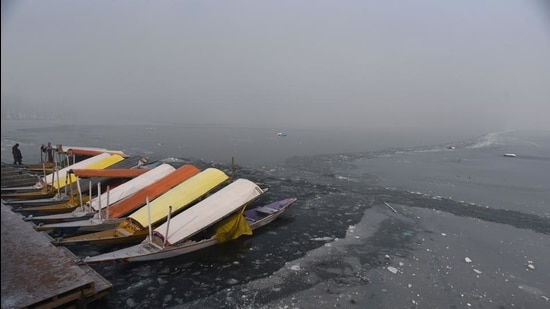 Shikara boats docked on a layer of ice after a large part of the Dal Lake froze over in Srinagar. (HT file photo)