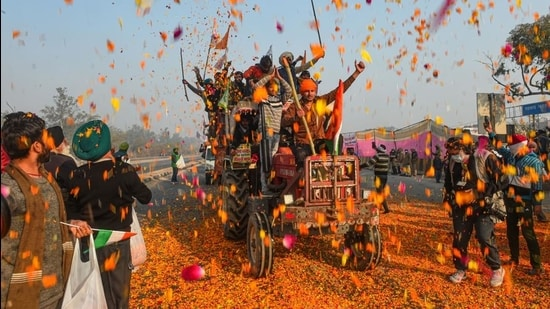 Farmers shower flower petals on fellow farmers riding on their tractors after breaking the police barricades at Singhu border during the 'Kisan Gantantra Parade' on Republic Day in New Delhi. (PT)