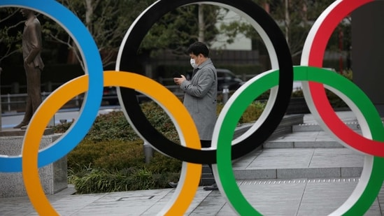 FILE PHOTO: A man looks at his mobile phone next to The Olympic rings in front of the Japan Olympics Museum in Tokyo, Japan, March 4, 2020. REUTERS/Stoyan Nenov/File Photo(REUTERS)