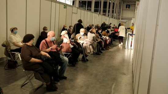 People wait to receive the coronavirus disease (Covid-19) vaccine at a temporary vaccination centre at the International Fair in Poznan, Poland. (Reuters)