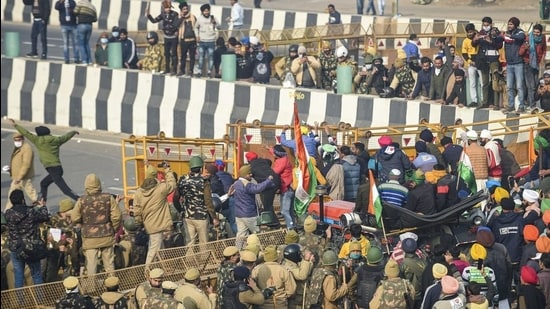 Farmers break the police barricades at the Ghazipur border as move towards Akshardham during their tractor rally on Republic Day in New Delhi, Tuesday, January 26. (PTi)