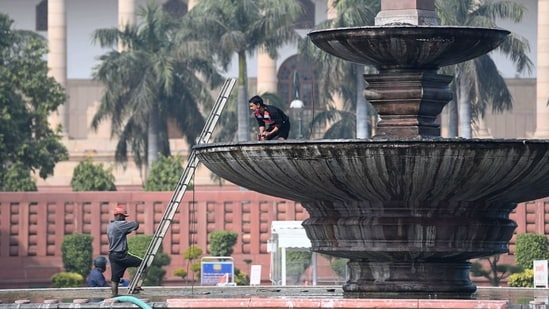 Men work near the Parliament in New Delhi. (AFP)
