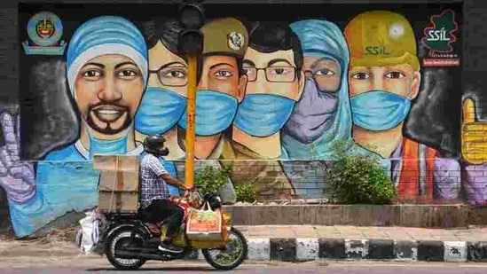 A motorist passes by a mural of frontline workers against coronavirus at RK Puram in New Delhi on July 25. Delhi's Covid-19 recoveries have outstripped new cases on almost all days this month barring a few exceptions, after ramped-up containment and testing efforts over the past month or so. (Sanchit Khanna / HT Photo)
