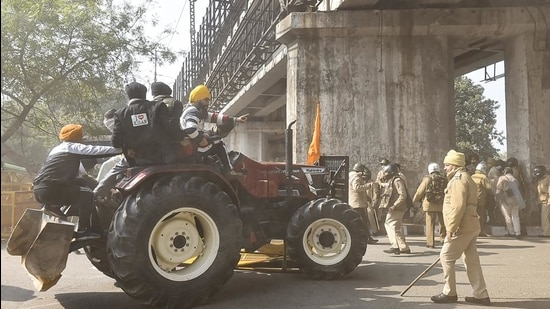 Farmers attempt to break a police barricade as they participate in the 'Kisan Gantantra Parade' during their ongoing protest against Centre's farm reform laws, on Republic Day, near Akshardham in New Delhi. (PTI)