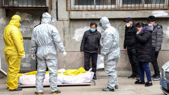 In this file photo, funeral home workers remove the body of a person suspected to have died from the coronavirus from a residential building in Wuhan in central China's Hubei Province. A relative of a coronavirus victim in China is demanding to meet a visiting World Health Organization expert team, saying it should speak with affected families who allege they are being muffled by the Chinese government. (AP)