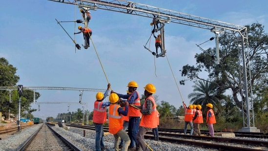 Workers on contract for Indian Railways, erect infrastructure for drawing electric cable lines over railway tracks for use by locomotives on the outskirts of Bangalore. (AFP)