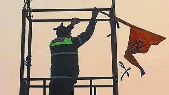 A security person at Red Fort takes off the Nishan Sahib flag that was hoisted there on Tuesday. (Sanchit Khanna/HT PHOTO)