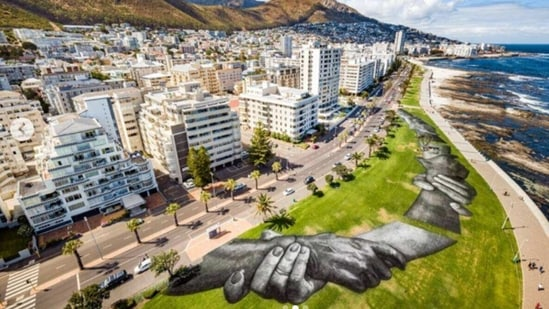"""The idea is to create the biggest human chain, to speak about togetherness and today in Cape Town this is the ninth step of that project,"" Saype, who was born Guillaume Legros. (Reuters)"