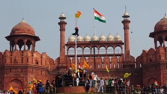 FILE - In this Tuesday, Jan. 26, 2021, file photo, a Sikh man hangs on to pole holding a Sikh religious flag along with a farm union flag at the historic Red Fort monument during a farmers protest against new farm laws in New Delhi, India. A sea of tens of thousands of farmers riding tractors and horses stormed India's historic Red Fort this week — a dramatic escalation of their protests, which are posing a major challenge to Prime Minister Narendra Modi's government. (AP Photo/Dinesh Joshi, File)(AP)