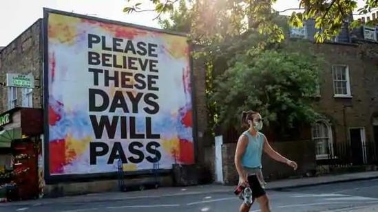"""A pedestrian walks past a billboard reading """"Please believe these days will pass"""" on Broadway Market in east London.(AFP File Photo )"""