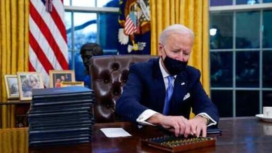 President Joe Biden reaches for a pen to sign his first executive order in the Oval Office of the White House in Washington.(AP)