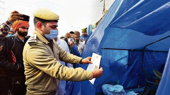 A policeman puts up a notice outside the tent of Rakesh Tikait and Jagtar Singh Bajwa at Ghazipur border on Thursday. (Raj K Raj/HT)