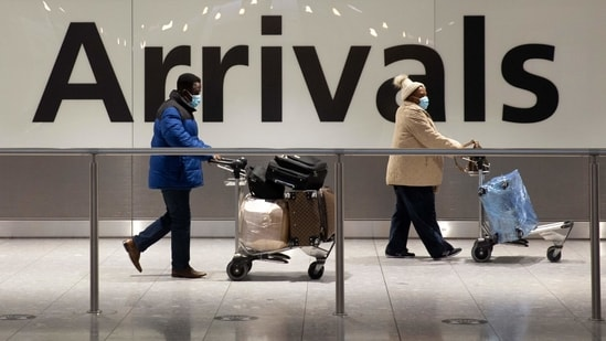 Arriving passengers walk past a sign in the arrivals area at Heathrow Airport in London on January 26, 2021. (AP)