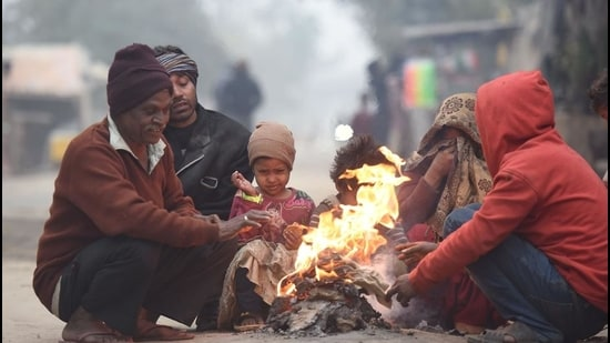 People warm themselves around a bonfire on a cold winter morning at Mayur Vihar, in New Delhi, earlier this week. (Raj K Raj/HT photo)