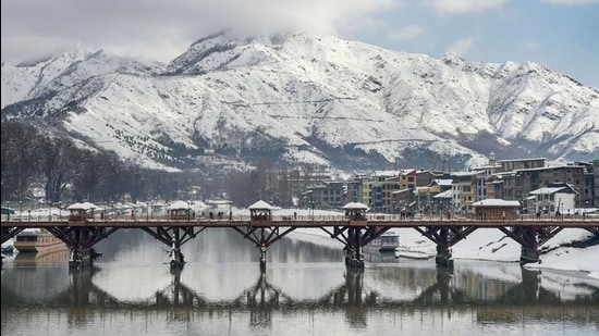 People walk across a footbridge as snowclad Zabarwan mountains are seen in the backdrop, after a heavy snowfall, in Srinagar, earlier this month. (File photo)