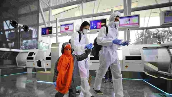 A family dressed in personnel protective suits walk towards security gates after checking in their baggage at Kempegowda International Airport in Bengaluru.(AP File Photo)