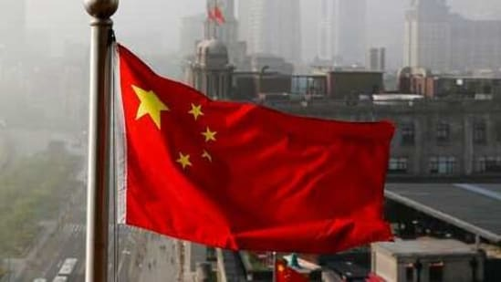 """FILE - In this April 14, 2016 file photo, a Chinese national flag flutters against the office buildings in Shanghai, China. Twitter locked China's U.S. Embassy account because of a tweet in support of China's policies on Muslims and ethnic minorities in the western Xinjiang, The tweet on Jan. 7, 2021 says Uygur women in Xinjiang have been emancipated and are no longer """"baby making machines."""" Twitter said it removed the tweet because it violates its policy on dehumanization. (AP Photo/Andy Wong, File)(AP)"""