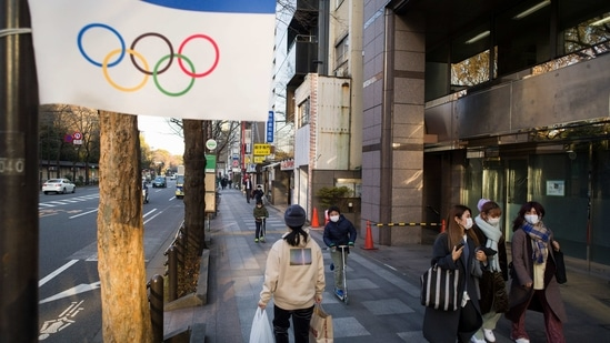 People wearing face masks walk and ride past an Olympics decoration installed along a street in Tokyo.(AP)