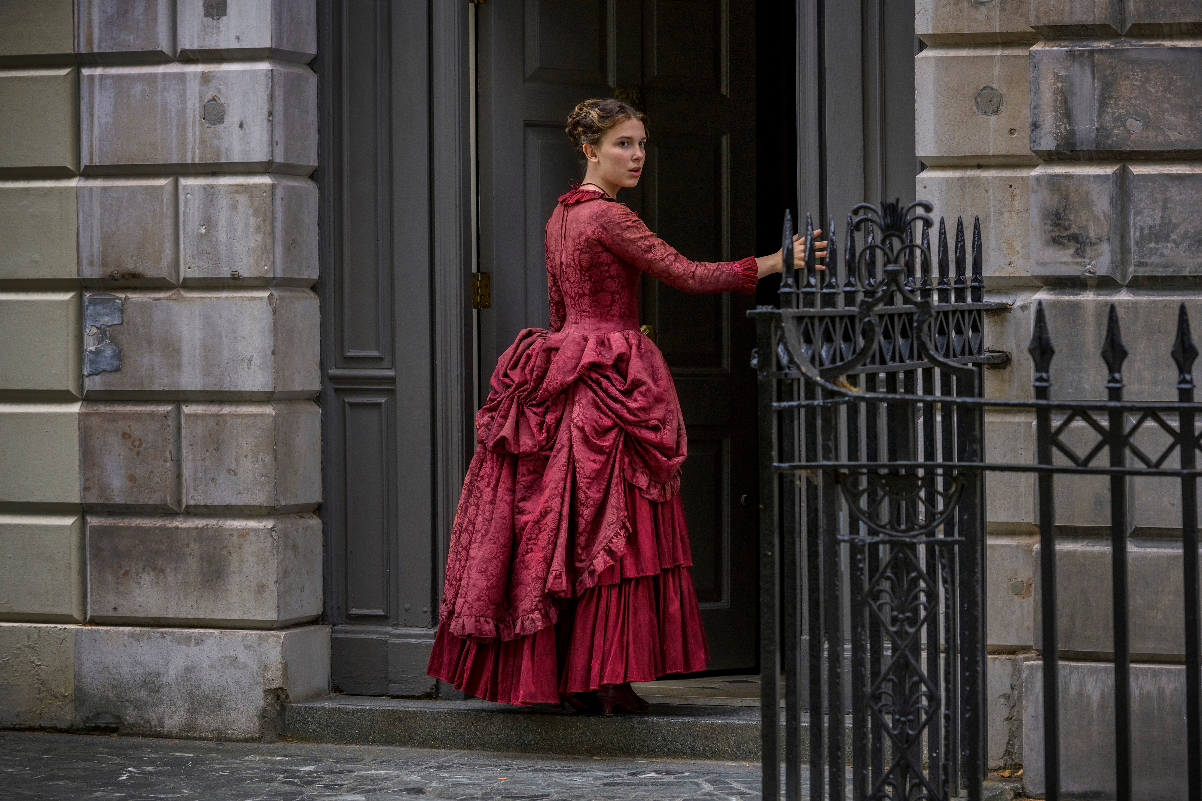 Millie Bobby Brown wearing a Victorian gown with cage-like hip modulator in the movie Enola Holmes