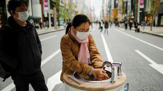 A shopper washes her hands using a mobile handwashing machine called 'WOSH', installed to prevent the spread of the Covid-19 in Tokyo. (REUTERS)
