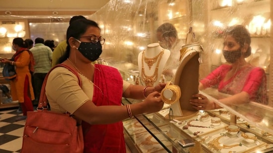 FILE PHOTO: Woman looks at a gold necklace at a jewellery showroom during Dhanteras, a Hindu festival associated with Lakshmi, the goddess of wealth, amidst the spread of COVID-19 in Kolkata, India, November 13, 2020. REUTERS/Rupak De Chowdhuri/File Photo(REUTERS)