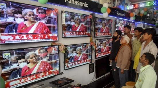 People watch finance minister Nirmala Sitharaman presenting Union Budget 2021-21 on television sets, at an electronics store in Prayagraj on Monday. (PTI)