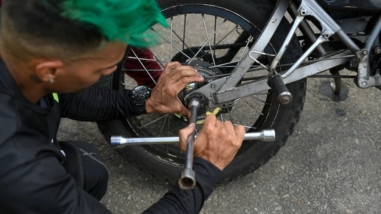 Motorcycle stuntman Pedro Aldana fixes his brakes during an exhibition in the Ojo de Agua neighborhood of Caracas, Venezuela. The 33-year-old makes a living with his shows, inspiring his young fans who flock to his shop, where he teaches them to change the oil and tune up their bicycles. (AP)