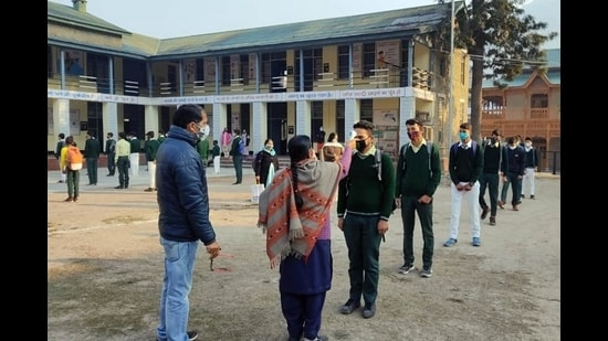 Teachers conducting thermal screening at a school in Mandi on Monday, 10 months after educational institutions were closed due to the Covid-19 pandemic. (HT Photo)