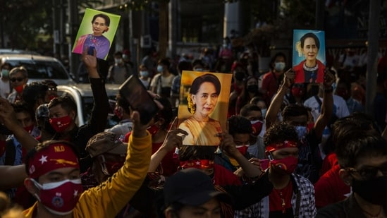 Demonstrators hold up images of Aung San Suu Kyi during a protest outside the Embassy of Myanmar in Bangkok, Thailand,(Bloomberg)