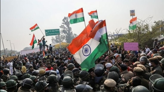 People shout anti-farmer slogans and wave India's national flags as police officers try to stop them, at a site of the protest against farm laws at Singhu border near New Delhi on January 29. (REUTERS)