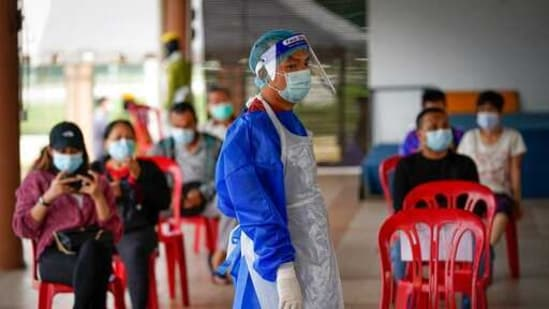 A medical worker wearing protective suits stand beside people waiting for their turn for coronavirus testing at a center for private Covid-19 testing in Petaling Jaya, Malaysia,(AP)