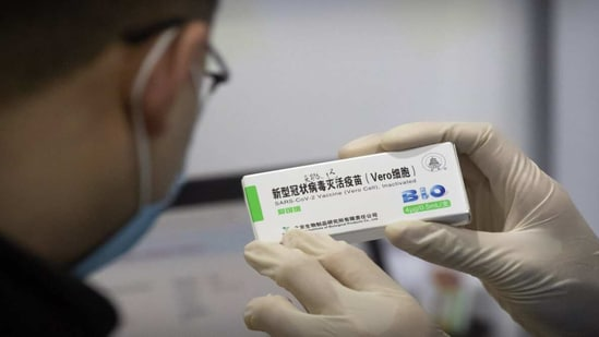 A medical worker shows the box for a coronavirus vaccine to a patient at a vaccination facility in Beijing.(AP Photo)