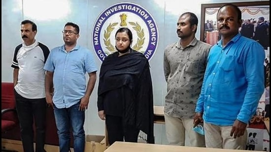 Kerala gold smuggling case accused Swapna Suresh and Sandeep Nair (middle) after they were arrested by the NIA in on July 11, 2020. (File photo)