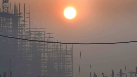 The rising sun seen over a construction site on a foggy morning at Pragati Maidan, New Delhi. (Arvind Yadav/ Hindustan Times)