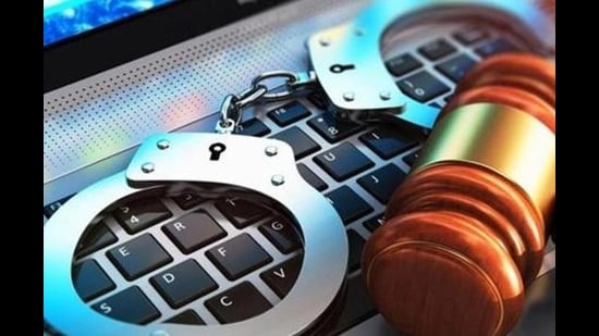 Creative abstract cyber crime, online piracy and internet web hacking concept: 3D render illustration of the macro view of metal handcuffs and wooden judge mallet, gavel or hammer on laptop notebook computer keyboard with selective focus effect (Getty Images/iStockphoto)