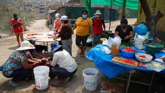 Residents prep donated vegetables at a soup kitchen in the Villa Maria shantytown of Lima, Peru, Tuesday, Feb. 2, 2021, amid a second complete lockdown in less than a year.(AP Photo)