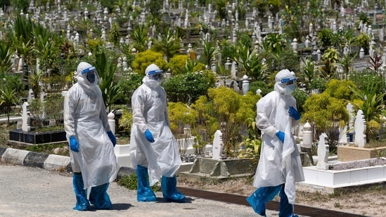 Workers wearing personal protective equipment (PPE) leave after burying a victim of the coronavirus disease at a Muslim cemetery in Gombak, outskirts of Kuala Lumpur, Malaysia.(AP)