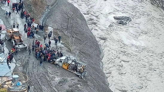 Rescue operations underway near Dhauliganga hydropower project after a glacier broke off in Joshimath causing a massive flood in the Dhauli Ganga river in Chamoli district of Uttarakhand.(PTI)