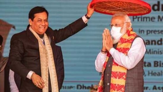 Assam Chief Minister Sarbananda Sonowal, left, greets Indian Prime Minister Narendra Modi by holding a traditional Assamese Japi above his head during a public rally in Dhekiajuli, Assam, India, Sunday, Feb. 7, 2021. (AP)