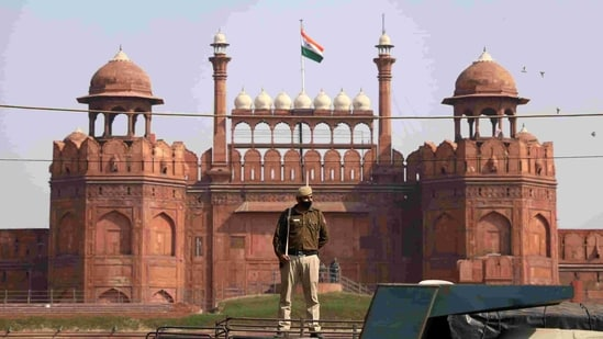 A police personnel stands guard in front of Red Fort during a roadblock-protest by farmers against the new farm laws, at Red Fort in New Delhi on Saturday. (ANI Photo)