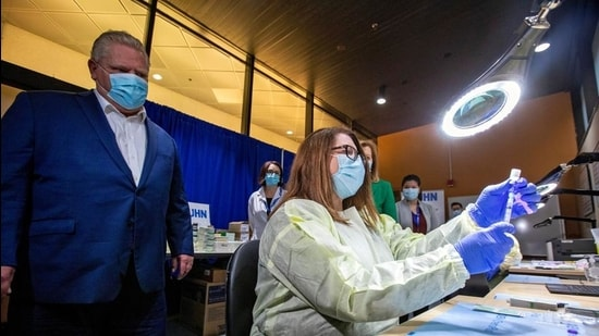 Ontario Premier Doug Ford watches a healthcare worker prepare a Pfizer-BioNTech coronavirus disease vaccine at The Michener Institute, in Toronto, Canada on January 4. (Reuters file)