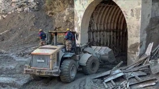 ITBP personnel use machinery to clear muck as they try to enter a tunnel to rescue trapped workers of a power plant, in Tapovan area of Uttarakhand on Monday.(AP Photo)