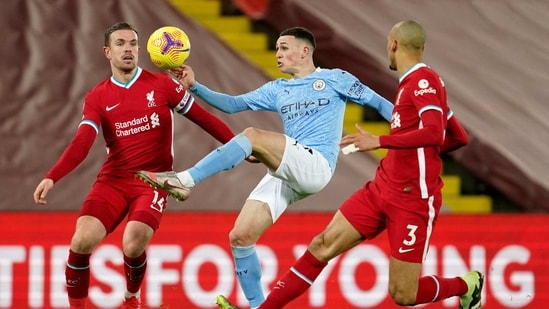 Liverpool: Manchester City's Phil Foden controls the ball between Liverpool's Jordan Henderson, left, and Liverpool's Fabinho during the English Premier League soccer match between Liverpool and Manchester City at Anfield Stadium, Liverpool.(AP)