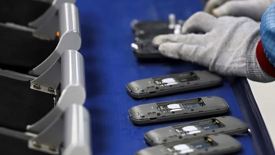 A worker assembles mobile phones.(Bloomberg)