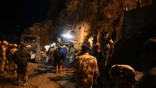 Indian army and rescue teams stand outside the entrance of a tunnel blocked with mud and debris during rescue operations in Tapovan of Chamoli district.(AFP)