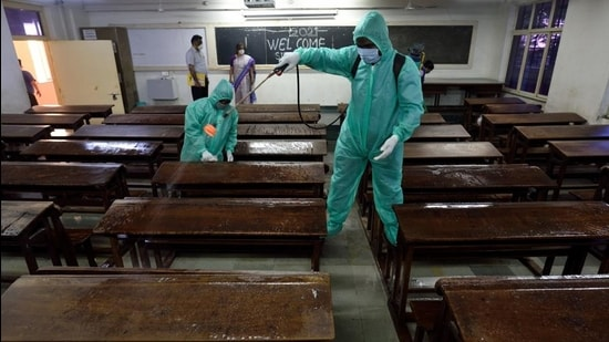 Employees in PPE kits sanitise a classroom at SIES College in Sion, Mumbai, on Wednesday. (Satish Bate/HT Photo)