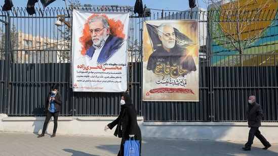 Iranians walk past a poster depicting late Revolutionary Guards commander Qasem Soleimani (R) and nuclear scientist Mohsen Fakhrizadeh, assassinated last month, in the capital Tehran.(AFP)